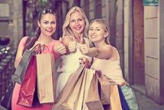 Amies tenant des sacs en papier d'achats Photo stock