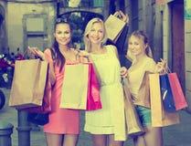 Amies tenant des sacs en papier d'achats Photographie stock libre de droits