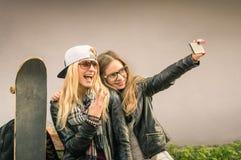 Amies urbaines de hippie prenant un selfie dans la ville Photos stock