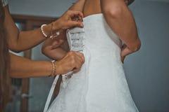 A amiga da noiva ajuda a vestir um vestido 1914 Fotos de Stock Royalty Free