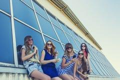 Amiga das mulheres nos óculos de sol com os telefones no backg da construção Fotografia de Stock Royalty Free