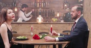 Amiga e noivo em um jantar que tem uma conversação filme