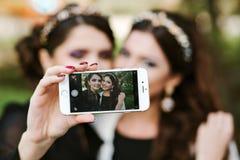 Amiga que hace un selfie Las muchachas en el partido que toma imágenes de ellos mismos en el teléfono Las mujeres forman elegante Fotos de archivo