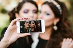 Amiga que hace un selfie Las muchachas en el partido que toma imágenes de ellos mismos en el teléfono Las mujeres forman elegante Imagen de archivo libre de regalías