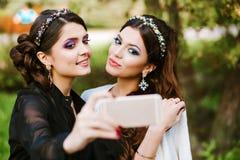 Amiga que hace un selfie Las muchachas en el partido que toma imágenes de ellos mismos en el teléfono Las mujeres forman elegante Imagen de archivo