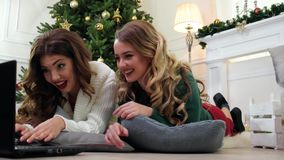 A amiga que usa o portátil, meninas obtém o prazer da comunicação em linha, em antecipação aos feriados de inverno de video estoque