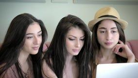 A amiga três bonita paga a compra em linha em seu portátil conceito de descontos sexta-feira preta do feriado vídeos de arquivo