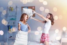 Amigas adolescentes felices que luchan las almohadas en casa Imagen de archivo libre de regalías