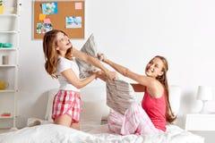 Amigas adolescentes felices que luchan las almohadas en casa Imágenes de archivo libres de regalías