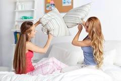 Amigas adolescentes felices que luchan las almohadas en casa Fotos de archivo