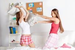 Amigas adolescentes felices que luchan las almohadas en casa Fotografía de archivo