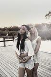 Amigas adolescentes pelo lago Fotografia de Stock Royalty Free