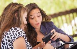 Amigas adultas novas entusiasmado que usam seu telefone esperto fotos de stock royalty free