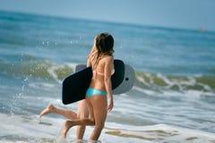 Amigas atléticas sanas de la persona que practica surf con los cuerpos del ajuste que llevan a cabo a tableros Fotografía de archivo