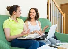 Amigas de sorriso que fazem trabalhos de casa Imagem de Stock