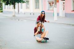 Amigas de sorriso que skateboarding e que têm o divertimento junto na rua imagens de stock