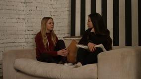Amigas diversas relaxado que conversam no sofá vídeos de arquivo
