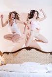 2 amigas divertidas hermosas, 2 mujeres atractivas atractivas que tienen salto que sorprende de la diversión arriba en sus pijama Foto de archivo libre de regalías