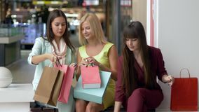 Amigas em vestuários coloridos depois que comprando discuta suas compras junto ao se sentar na alameda durante o preto video estoque