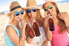 Amigas en comida campestre en la playa Fotografía de archivo libre de regalías