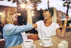 Amigas exuberantes felices que dan altos cinco Imágenes de archivo libres de regalías