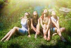 Amigas felices que se sientan en verde del verano Fotos de archivo libres de regalías
