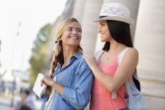 Amigas felizes que andam através da cidade durante férias Imagens de Stock