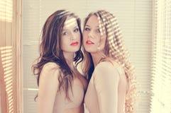 2 amigas hermosas de las mujeres jovenes en trajes corporales con los labios rojos que se oponen a la iluminación del sol Imagen de archivo libre de regalías