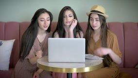 Amigas maravilhosas que fazem a compra em linha no portátil no café o riso de sorriso tem o divertimento video estoque