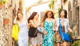 Amigas milenares multirraciais que andam e que falam na excursão velha da cidade - meninas felizes que têm o divertimento em torn fotos de stock