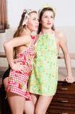 2 amigas modelas atractivas hermosas divertidas de la mujer joven que se colocan en delantales y que miran para arriba el espacio Imagen de archivo
