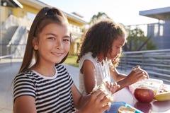 Amigas na tabela do almoço escolar, uma sorrindo à câmera imagens de stock royalty free