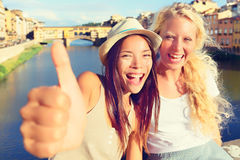Amigas nos polegares de doação felizes da cidade acima Fotos de Stock Royalty Free
