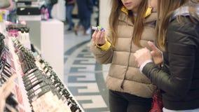 Amigas passam por vários produtos de cosméticos decorativos em uma prateleira vídeos de arquivo