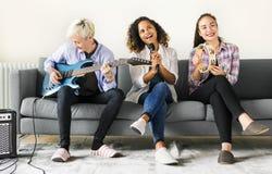 Amigas que apreciam com canto e jogo da música imagem de stock royalty free