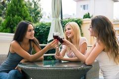 Amigas que bebem o vinho tinto fora no restaurante Foto de Stock