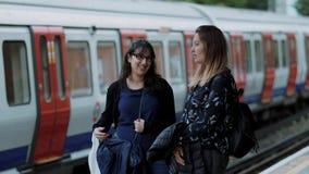 Amigas que esperam em uma plataforma de Londres no subsolo vídeos de arquivo