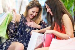 Amigas que hacen compras para la ropa en tienda imagen de archivo