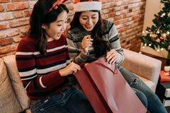 Amigas que olham no saco de compras vermelho grande foto de stock