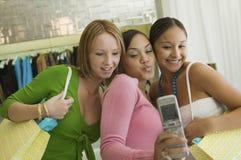 3 amigas que presentan para la imagen del teléfono de la cámara en tienda de ropa Imagen de archivo