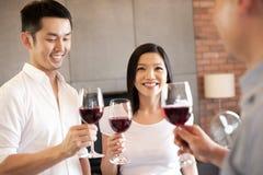 Amigo asiático de la familia que se coloca con el vino Imágenes de archivo libres de regalías