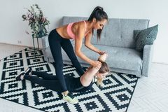 Amigo de ajuda da mulher apta no exercício de esticão traseiro em casa imagens de stock royalty free