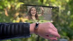 Amigo de la llamada de la mano del atleta de la muchacha que aparece en holograma Reloj futurista y tecnológico Parque en fondo almacen de video