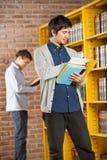 Amigo de Reading Book While del estudiante que se coloca adentro Imagen de archivo