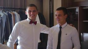 Amigo do noivo nas camisas brancas para ajudar a amarrar o laço para preparar que ir pronto à noiva filme