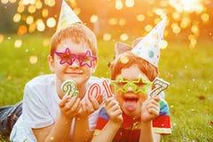 Amigo feliz de los niños en el partido del carnaval, mintiendo en una hierba verde en s Foto de archivo libre de regalías
