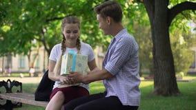 Amigo que da la actual caja a la muchacha adolescente en el parque, sorpresa el b-día, celebración almacen de metraje de vídeo