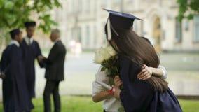 Amigo que espera graduado de la hembra de la universidad para a venir, dando las flores y el abrazo almacen de metraje de vídeo