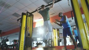 Amigo que motiva al hombre joven durante el entrenamiento intensivo en gimnasio, forma de vida sana almacen de video
