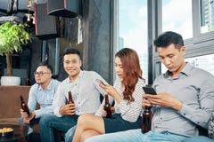 Amigos étnicos com cerveja e smartphones fotografia de stock royalty free